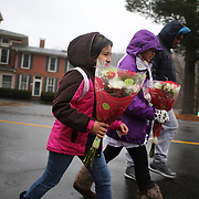 Young girls head to place flowers at the shrine set up at the school sign in Sandy Hook after the mass shootings at Sandy Hook Elementary School, Newtown, Connecticut, USA. 16th December 2012. Photo Tim Clayton
