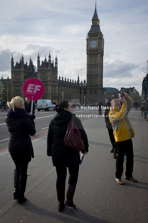 A foreign tour leader walks towards Big Ben over Westminster Bridge carrying an Education First sign.