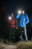Full length portrait of male backpackers with flashlights in field at night