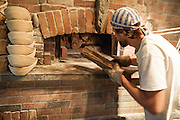 Jamestown, RI - 7 May 2007. Andrea Colognese of The Village Hearth Bakery and Cafe, building a fire in the bakery's oven. Colognese built the oven himself.