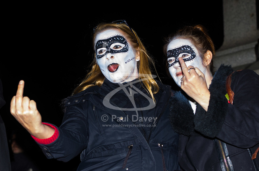 London, November 05 2017. Anti-capitalists gather in Trafalgar Square, London for the annual 'Million Mask March' which happens on November 5th every year, with many of the protesters donning 'V' For Vendetta Guy Fawkes masks. Past marches have turned violent with police horses shot by fireworks and police vehicles burned. PICTURED: Two women make obscene gestures from the plinth of Nelson's column in Trafalgar Square. © Paul Davey