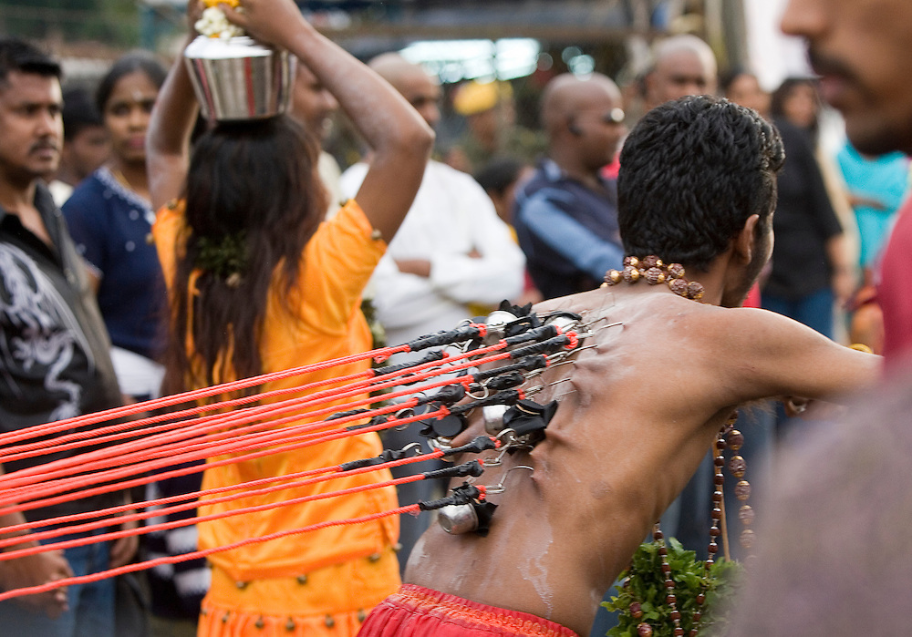 "A hindu devotee with hooks attached on his back, walks to the sacred Batu Caves temple during the Thaipusam festival in Kuala Lumpur, Malaysia. Hindu devotees celebrate Thaipusam festival in honour of the Lord Murugan (also known as Lord Subramaniam). Thousands of Hindu devotees carried the milk pots and ""kavadi"" (a gaily decorated wooden or metal frame) walk barefoot up the temple's 272 steps to undergo penance in fulfilling vows made to Lord Murugan for answering their prayers."