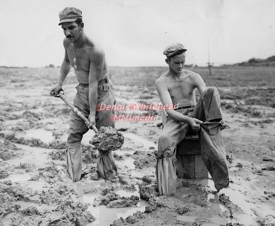 Marine tankmen make like ducks as they wear sandbags on their feet in an effort to combat the deep Okinawa mud. Struggling with the ooze are Pvt. Byron B. Barber and PFC Melvin E. Johnson.