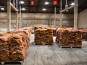 "16 DECEMBER 2014 - CHUM SAENG, RAYONG, THAILAND: Smoked rubber sheets in a warehouse on a large rubber plantation near Chum Saeng, Thailand. Thailand is the second leading rubber exporter in the world. In the last two years, the price paid to rubber farmers has plunged from approximately 190 Baht per kilo (about $6.10 US) to 45 Baht per kilo (about $1.20 US). It costs about 65 Baht per kilo to produce rubber ($2.05 US). Prices have plunged 5 percent since September, when rubber was about 52Baht per kilo. Some rubber farmers have taken jobs in the construction trade or in Bangkok to provide for their families during the slump. The Thai government recently announced a ""Rubber Fund"" to assist small farm owners but said prices won't rebound until production is cut and world demand for rubber picks up.    PHOTO BY JACK KURTZ"