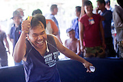 11 APRIL 2010 - PLA PAK, NAKHON PHANOM, THAILAND: A bookie reacts to his long shot win after the bird he bet on, which passed out in the first round of his fight, came back to win in the last round. Cockfighting is enormously popular in rural Thailand. A big fight can bring the ring operator as much as 200,000 Thai Baht (about $6,000 US), a large sum of money in rural Thailand. Fighting cocks live for about 10 years and only fight for 2nd and 3rd years of their lives. Most have only four fights per year. Fighting cocks in Thailand do not wear the spurs or razor blades that they do in some countries and most times the winner is based on which rooster stops fighting or tires first rather than which is the most severely injured. Although gambling is illegal in Thailand, many times fight promoters are able to get an exemption to the gambling laws and a lot of money is wagered on the fights. Many small rural communities have at least one cockfighting arena.   PHOTO BY JACK KURTZ
