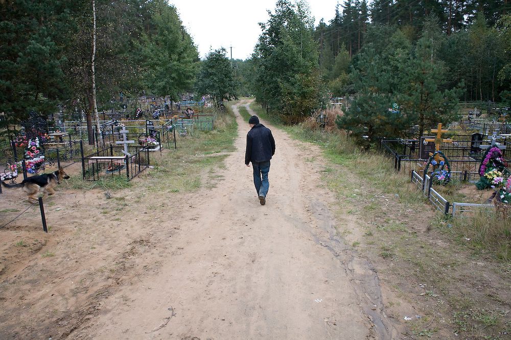 Valera, a former drug user who is now in a rehabilitation program run by the orthodox church, walks his dog through a cemetery near the organization's live-in retreat in Sapernoe, Russia, on Saturday, September 15, 2007. About a dozen people at a time live and work at the remote farm, about two hours from St. Petersburg, for a free one year course of treatment.