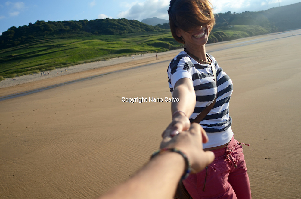 Young woman plays and dances on the beach, holding hands with the photographer