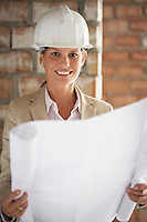 Architect holding plans at construction site