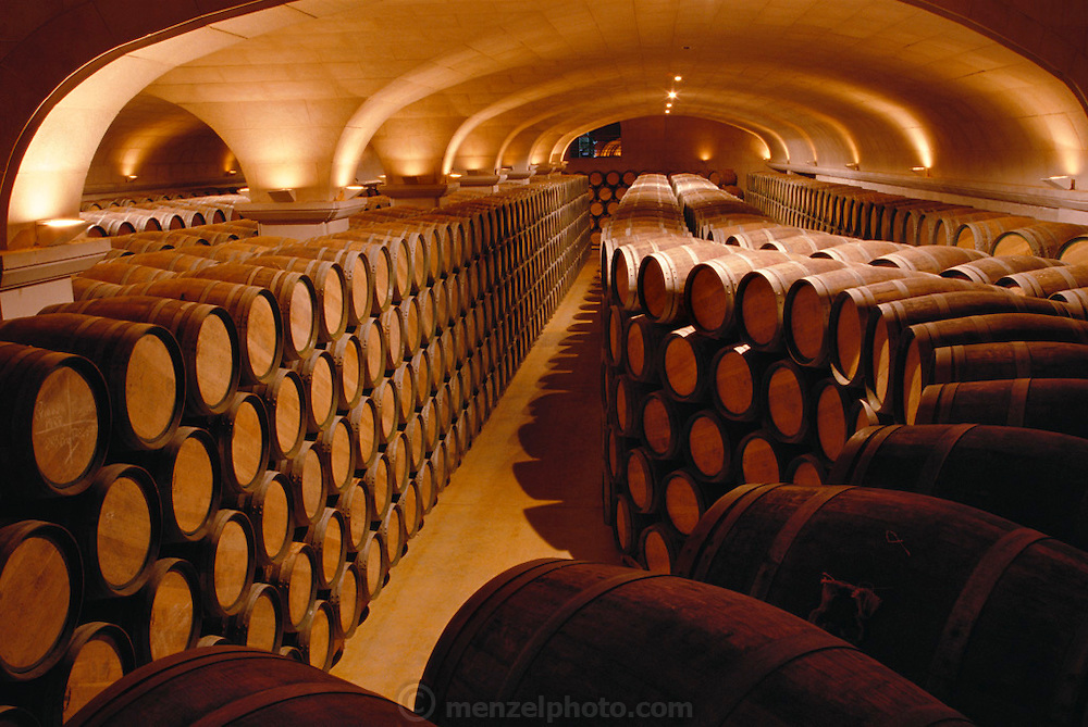 Thousands of wine barrels in the aging cellars of the ultra-contemporary Bodegas Campillo in Laguardia, Spain. They use stainless steel fermentation tanks but employs both modern and traditional methods in the winemaking process. Their aging barrels are both American and French oak. The bodegas' youngest wine is four years old. The winery maintains an area where buyers of quantities of the wine can store what they buy. Because of automation, there are only five fulltime employees running the extensive entire daily operation. Few year round workers are needed. La Rioja, Laguardia, Spain.