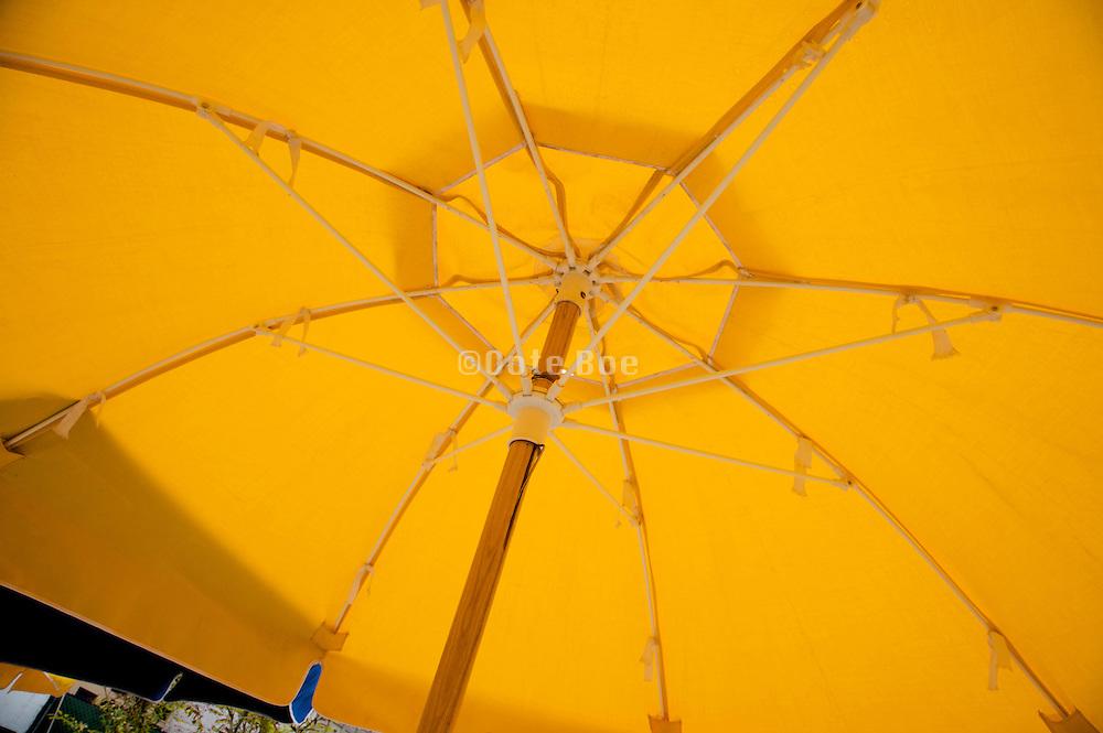the inside of a big yellow beach umbrella