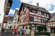 A family walks by Haus Vetter, a half-timbered house on Bodenseeradweg in Stein am Rhein village, Schaffhausen Canton, Switzerland, Europe.