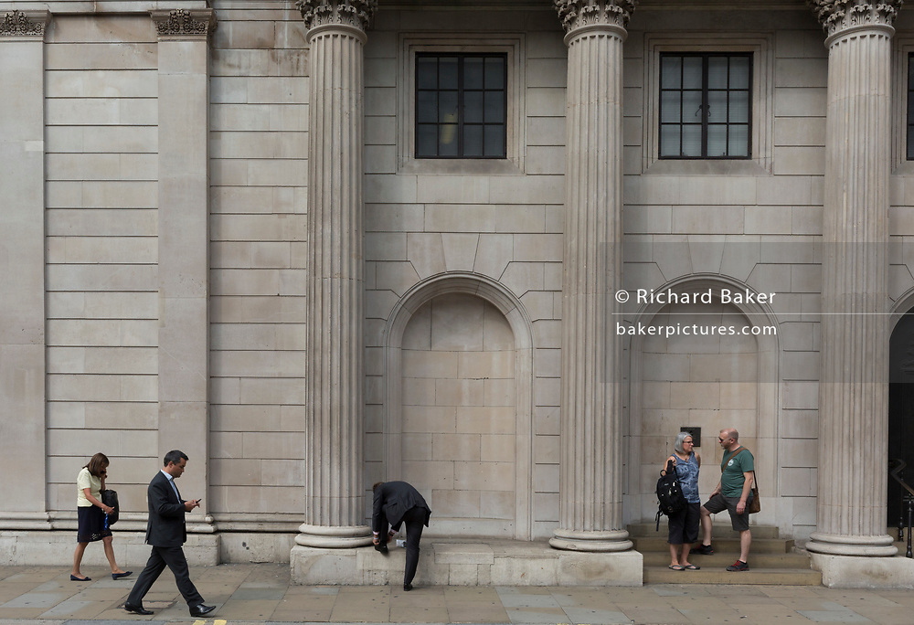 """Londoners walk, tie a loose lace and stand beneath the columns and pillars of the Bank of England on Threadneedle Street in the City of London - the capital's financial district, on 3rd September 2018, in London England. The Bank of England, is the central bank of the United Kingdom and the model on which most modern central banks have been based. Established in 1694, it is the second oldest central bank in the world. Sir Herbert Baker's rebuilding of the Bank, demolishing most of Sir John Soane's earlier building, was described by architectural historian Nikolaus Pevsner as """"the greatest architectural crime, in the City of London, of the twentieth century""""."""