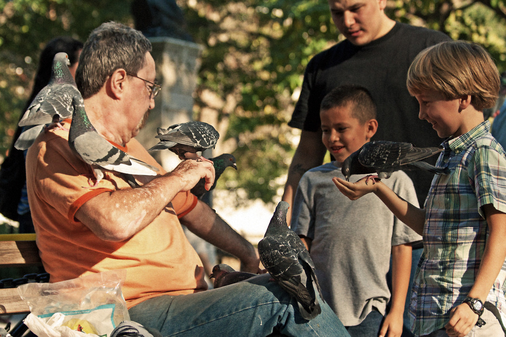 NYC street photo of birdman and kids feeding birds in Washington Square Park.