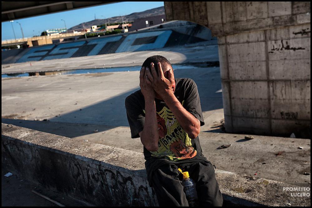 'El Mai', un hombre que vive bajo los puentes en El Bordo, Tijuana, grita mientras bebe un mezcal barato, el 17 de agosto de 2014. (FOTO: Prometeo Lucero)