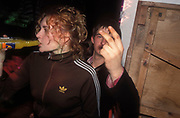 A teenager sticking two fingers up, whilst his girlfriend drinks an alcopop, UK 2004<br />