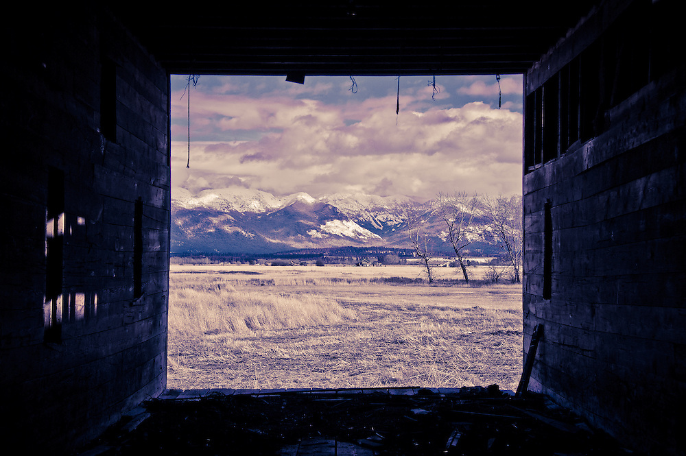 View through istoric barn at Blasdel Waterfowl Production Area to Swan Mountains