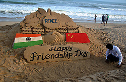 August 5, 2017 - Puri, Orissa, India - Visitors look near to a sand sculpture creating by sand artist Sudarshan Pattnaik to spread message about China-India friendship on the International Friendship Day at the Bay of Bengal Sea's eastern coast beach at Puri, 65 km away from the eastern Indian state Odisha's capital city Bhubaneswar. (Credit Image: © Str/NurPhoto via ZUMA Press)