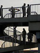 people climbing a circular stair set against a colorful evening sky