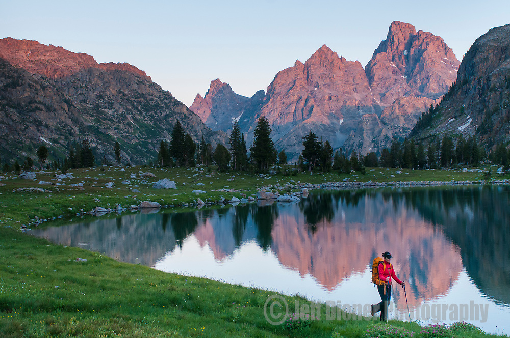 A young woman hikes along the shore of Lake Solitude in Grand Teton National Park, Jackson Hole, Wyoming.