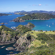 An aerial view of A yacht's moored in a secluded bay in the Bay of Islands, North Island, New Zealand. .The Bay of Islands boasts a unique coastline sheltering over 150 small islands in its arms. Once a seafaring and whaling region the Bay of Islands is today a popular tourist destination recognised for it's cultural heritage as well as it's amazing scenery and wildlife. Small towns are scattered along the coastline. There are a lot of water-based activities, including kayaking, swimming with dolphins, game fishing and boating and whales and dolphins can often be seen in the bay. Bay of Islands, New Zealand, 16th November 2010. Photo Tim Clayton.