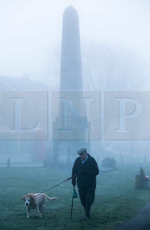 © Licensed to London News Pictures. 14/03/2014. Meriden, Coventry, UK. Dense fog covered the Midlands earlier today. Pictured, a man walking his dog in Meriden, near Coventry. Photo credit : Dave Warren/LNP