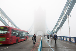© Licensed to London News Pictures. 11/12/2013. London, UK. Commuters and traffic cross Tower Bridge during thick fog this morning, 11 December 2013. Photo credit : Vickie Flores/LNP