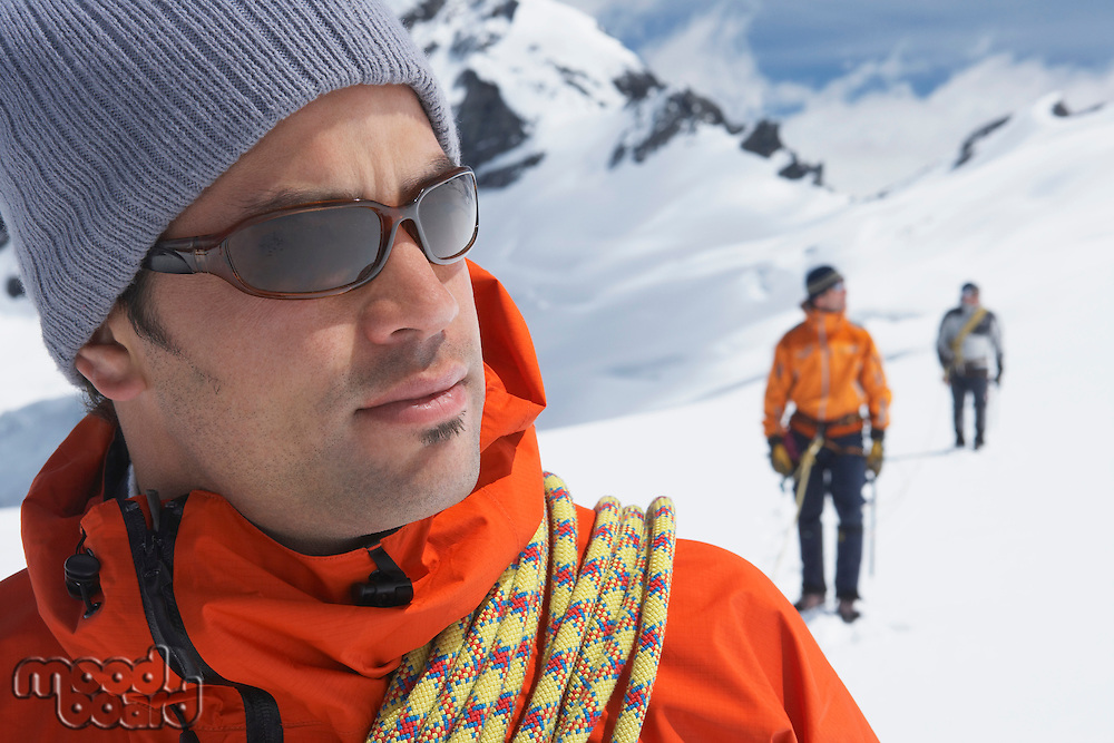 Hiker joined by safety line to two friends behind in snowy mountains