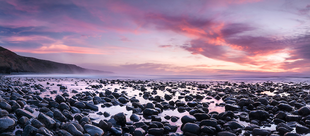 Sunset and low tide at praia do Canal, well known for its rounded stones.