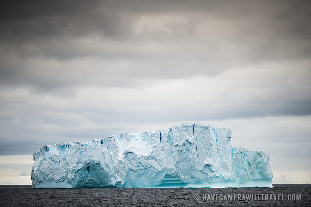 A large blue-green iceberg floats on the waters of the northern Antarctic Peninsula.