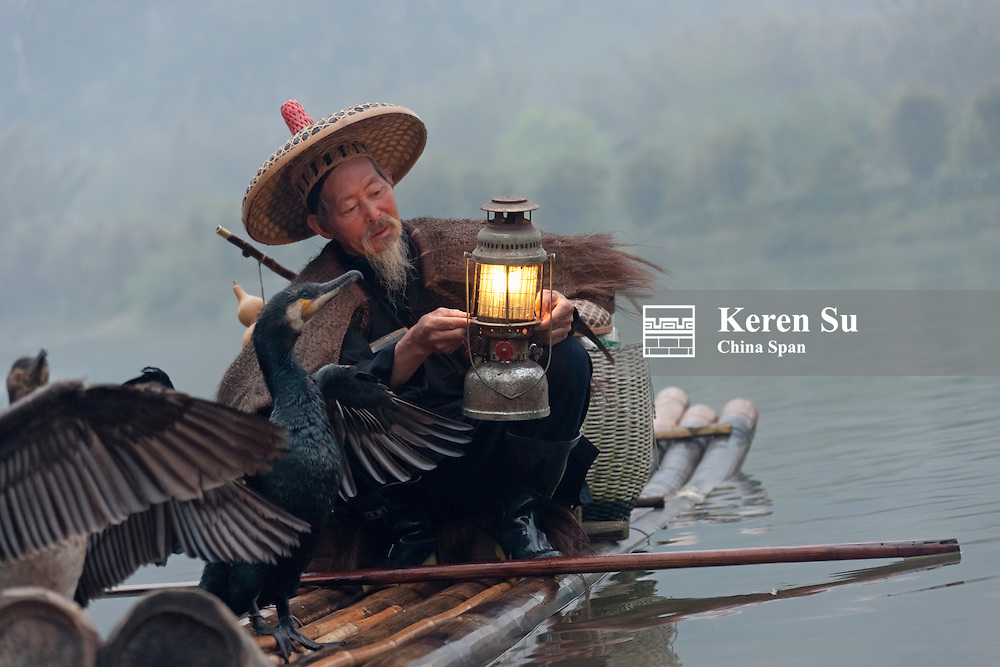 Fisherman wearing straw raincoat fishing with cormorants at dusk on the Li River, Yangshuo, Guangxi Province, China