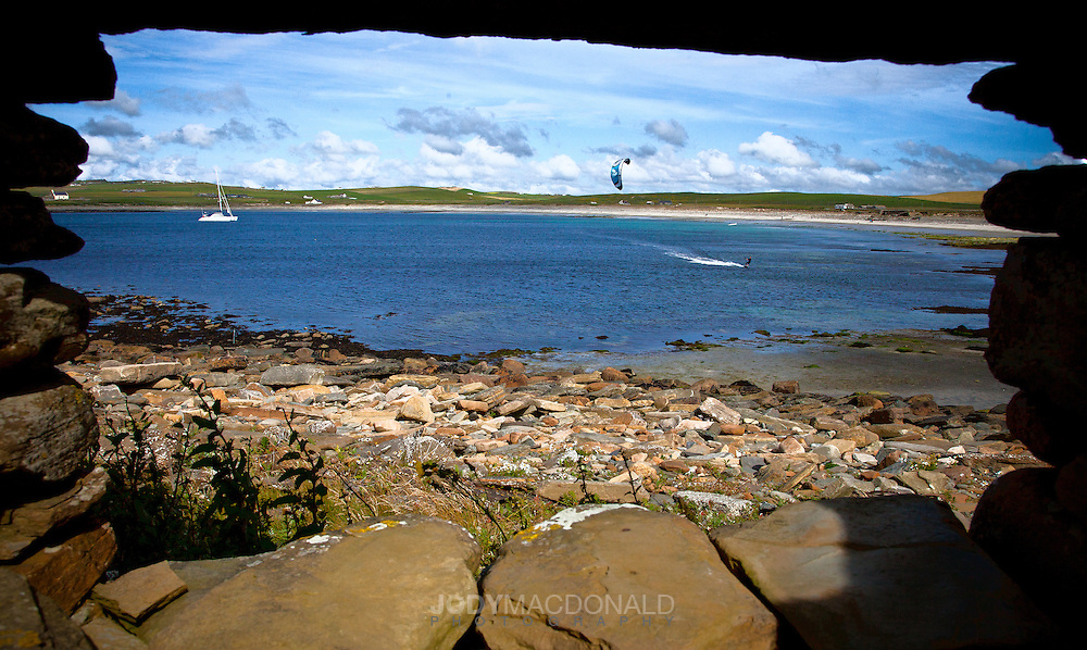 Looking through ancient window at kiteboarder with boat and beach in background