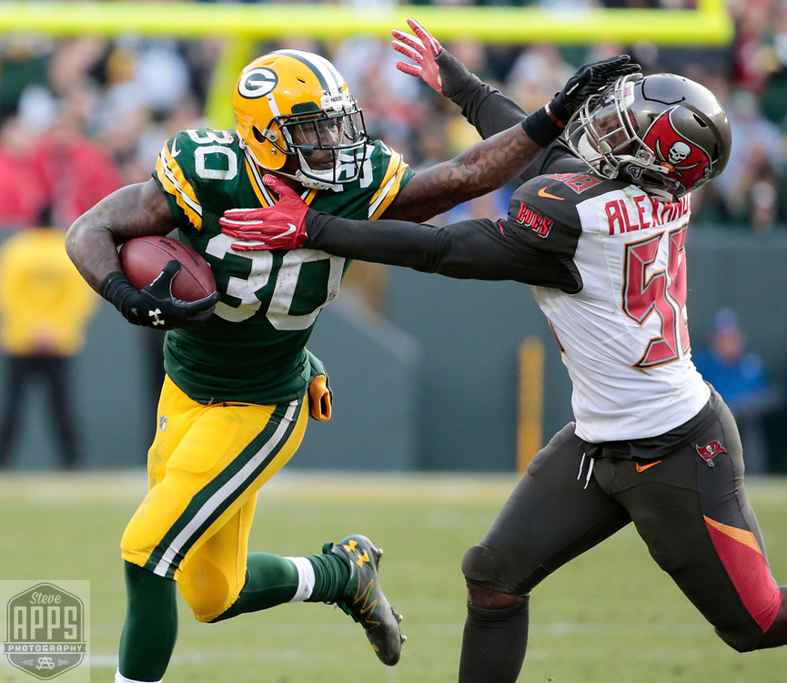 Green Bay Packers running back Jamaal Williams (30) stiff arms Tampa Bay Buccaneers middle linebacker Kwon Alexander (58) on a 18-yard pass in Overtime. <br /> The Green Bay Packers hosted the Tampa Bay Buccaneers at Lambeau Field in Green Bay,  Sunday, Dec. 3, 2017. The Packers won in 26-20 in Overtime.   STEVE APPS FOR THE STATE JOURNAL.