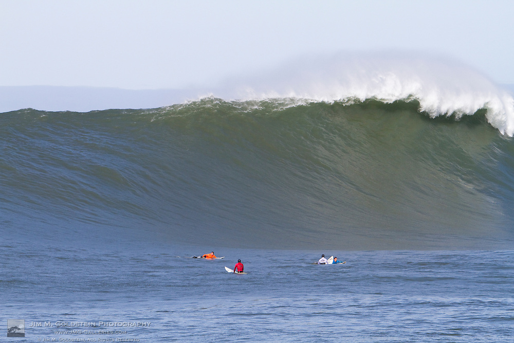 Surfers paddle to catch a giant wave during the early heats of the Mavericks Surf Contest held in Half Moon Bay, California on February 13, 2010