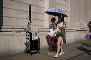 Young women shaded by an umbrella beneath the walls of the Bank of England during an unusual autumn heatwave on 13th September 2016, in the City of London, England.