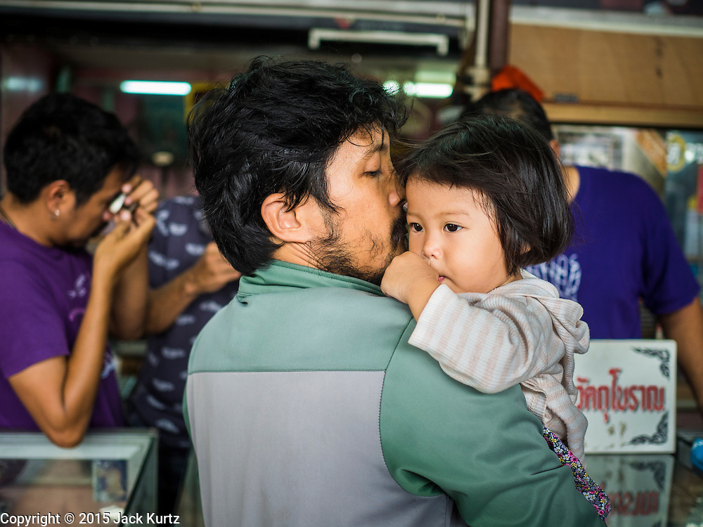 13 MAY 2015 - SAMUT SONGKRAM, SAMUT SONGKRAM, THAILAND:  A man and his daughter in the market in Samut Songkram, Thailand. The man was trying to sell some of his religious amulets to vendors in the market.        PHOTO BY JACK KURTZ
