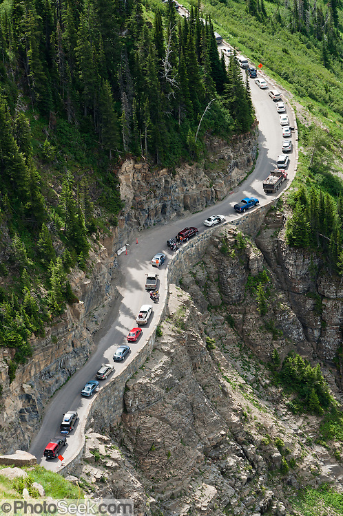 "Cars ascend the Going-to-the-Sun Road towards Logan Pass, seen from the Garden Wall Trail in Glacier National Park, Montana, USA. Since 1932, Canada and USA have shared Waterton-Glacier International Peace Park, which UNESCO declared a World Heritage Site (1995) containing two Biosphere Reserves (1976). Rocks in the park are primarily sedimentary layers deposited in shallow seas over 1.6 billion to 800 million years ago. During the tectonic formation of the Rocky Mountains 170 million years ago, the Lewis Overthrust displaced these old rocks over newer Cretaceous age rocks. Glaciers carved spectacular U-shaped valleys and pyramidal peaks as recently as the Last Glacial Maximum (the last ""Ice Age"" 25,000 to 13,000 years ago). Of the 150 glaciers existing in the mid 1800s, only 25 active glaciers remain in the park as of 2010, and all may disappear by 2020, say climate scientists."
