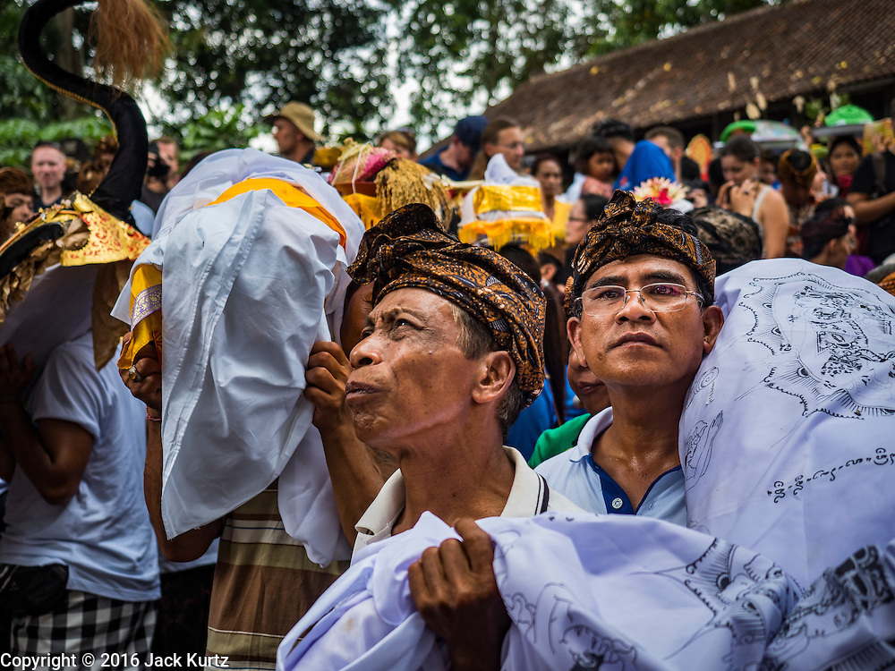 16 JULY 2016 - UBUD, BALI, INDONESIA:  Men carry the effigies that represent the people being cremated into the cremation ground during the mass cremation in Ubud. Local people in Ubud exhumed the remains of family members and burned their remains in a mass cremation ceremony Wednesday. Almost 100 people were cremated and laid to rest in the largest mass cremation in Bali in years this week. Most of the people on Bali are Hindus. Traditional cremations in Bali are very expensive, so communities usually hold one mass cremation approximately every five years. The cremation in Ubud concluded Saturday, with a large community ceremony.    PHOTO BY JACK KURTZ