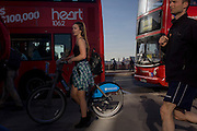 Girl cyclist on a Barlcays-sponsored Boris bike, crosses  southbound over London Bridge during the evening rush hour.