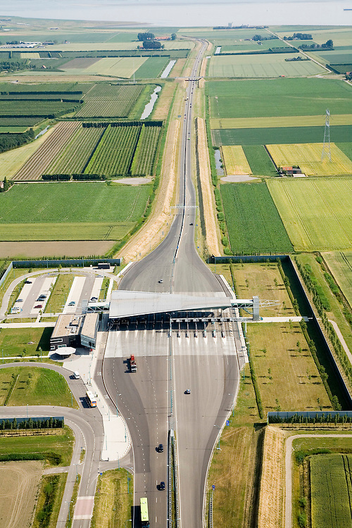 Nederland, Zeeland, Zuid-Beveland, 04-07-2006; luchtfoto : Borssele polder, tolplein Westerscheldetunnel, toegangsweg van de tunnel, richting Westerschelde (aan de horizon); aan weerszijden van deze toegangsweg zijn geluidswallen gebouwd om geluidsoverlast te voorkomen; deze geluidsschermen zijn in de vorm van dijken, passend in het omringende landschap (landschappelijke inpassing); privaat publieke samenwerking, PPS, planologie, verkeer en vervoer, mobiliteit, auto, infrastructuur, milieu; zie ook andere (lucht)foto's van deze lokatie, deevan de serie Panorama Nederland.luchtfoto (toeslag); aerial photo (additional fee required); .foto Siebe Swart / photo Siebe Swart