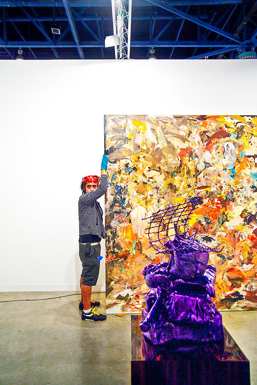 Worker installs absract expressionist painting at Art Basel Miami Beach 2008
