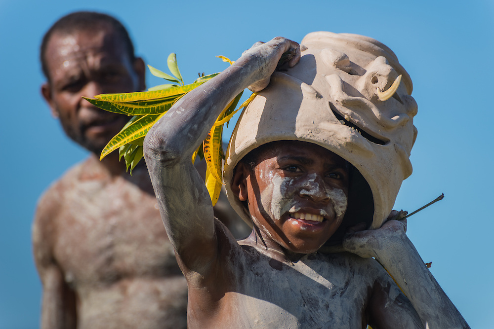 Boy from the Goroko mudmen tribe lifts his mask, Madang, Papoea new Guinea.