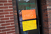 "A woman waits inside On Target Staffing in front of signs advertising a need for women temp workers on French Street in New Brunswick, NJ on April 18, 2013. Across America, temp work has become a mainstay of the blue-collar economy, leading to the proliferation of ?temp towns? ? places where it's difficult to find work except through a temp agency and where workers suffer wage theft, no benefits and high injury rates, all for jobs that may end tomorrow for any reason. .Signs read (not exact translation): ""Women needed, flexible schedules."" and ""Women to work $9. First and Second shifts."""