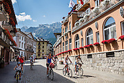 A family bicycles on a brick cobblestone street closed to cars in Cortina d'Ampezzo, Dolomites, Italy, Europe. The ski resort of Cortina d'Ampezzo (Ladin: Anpëz, German: Hayden, at 1224 meters/4016 feet) is surrounded by the Dolomites (or Dolomiti, part of the Southern Limestone Alps) at the head of Valle del Boite, in the Province of Belluno, Veneto region, Italy, Europe. Cortina gained worldwide fame after hosting the 1956 Winter Olympics. UNESCO honored the Dolomites as a natural World Heritage Site in 2009.
