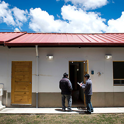Two Chinalco employees inspect newly built houses in the town of Carhuacoto in the central Peruvian Andes. Chinalco has built this town with 1050 new houses to relocate the residents of Morococha, where a large open pit mine will be built.