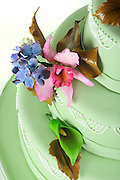 Detail of Pale Green Wedding Cake with pink and purple marzipan flowers