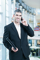 Businessman on mobile phone looking at camera