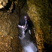 A man navigates past a waterfall at the exit of the caves while Black Water rafting in the Waitomo Glowworm Caves, Waitomo, North Island, New Zealand..The Legendary Black Water Rafting Company is New Zealand's first black water adventure tour operator which takes tourists through the  Ruakuri Cave at Waitomo..The five hour expedition combines abseiling the 35 metre entrance. climbing, a flying fox. black water tubing, leaping and floating through Ruakuri Cave and observing glow worms. The journey concludes  into the sunlight of the Waitomo forest..Waitomo, New Zealand,, 14th December  2010 Photo Tim Clayton