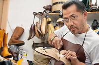 Portrait of a skilled cobbler cutting shoe sole in workshop