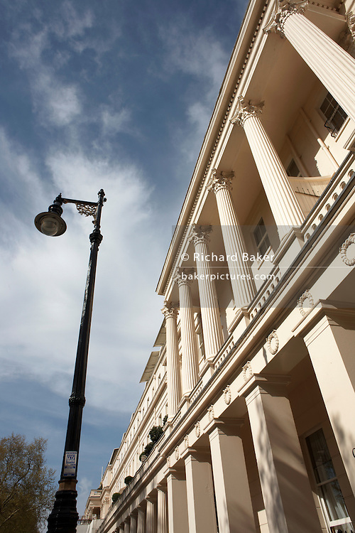 A vertical version that shows the Corinthian columns and covered doorways of exclusive and classically-designed properties in London's famous Eaton Square Belgravia, SW1, owned by Grosvenor Estate. It is a bright spring day with a blue city sky and high, thin clouds. The sun shines on the cream-coloured architectural features and some shadows from trees opposite can be seen on the lower upright pillars and an ornate lamp post. Eaton Square is one of London's three garden squares built by Thomas Cubitt and the Grosvenor family when they developed the main part of Belgravia from 1826 until 1855. Belgravia attracts actors, politicians, ambassadors, big-budget bankers, traders and Prime Ministers like Neville Chamberlain and Stanley Baldwin at number 93..