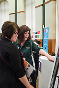 "Kelly Martin and UCM's Gabrielle Johnston look at a ""find the branding error"" game during the CCN Expo in Walter Hall Rotunda on Wednesday, May 13, 2015.  Photo by Ohio University  /  Rob Hardin"